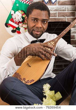 African American Man With Musical Instrument Dombra By Fireplace. Christmas And New Year