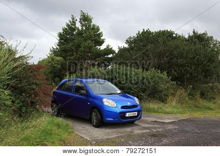 Blue Nissan Micra near trees.