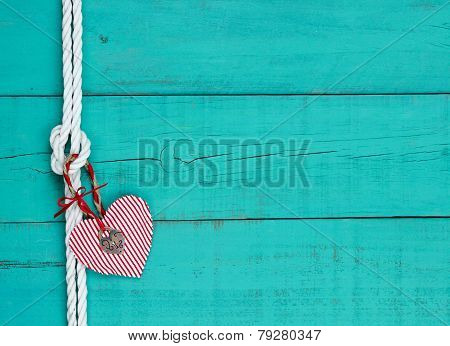 Red heart and lock hanging on rope knot against antique teal blue wooden background