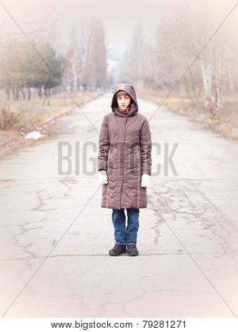 Young woman standing on the road.