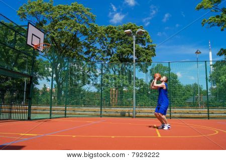 Young man shoots basketball ball