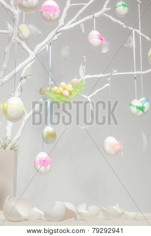 White easter eggs with colorful  ribbons on tree branches in vase