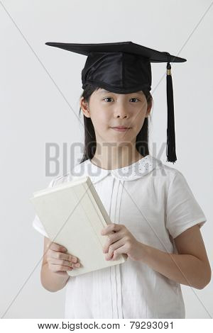 chinese girl with mortar board holding a book