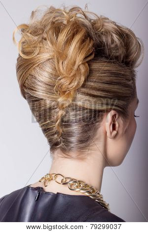 Beautiful woman with evening salon hairdo. Complicated hairstyle for party
