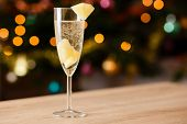 foto of sparkling wine  - A glass of sparkling wine with pineapple on the table - JPG