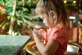 image of internet-cafe  - girl play phone in cafe during waiting food - JPG