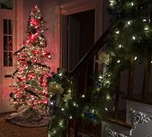 foto of bannister  - Christmas tree at the base of the stairs with lighted garland draped over the bannister - JPG