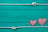 stock photo of candy cane border  - Red and white candy cane striped hearts and silver heart lock by rope with knot border on blank antique teal blue shabby wooden background - JPG