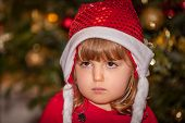 stock photo of sad christmas  - Sad and upset Christmas girl with the Christmas tree in the background - JPG