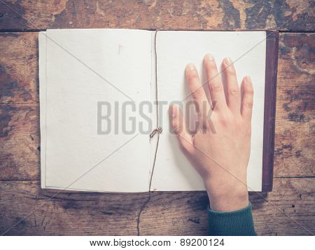 Hand And Notepad On A Wooden Table