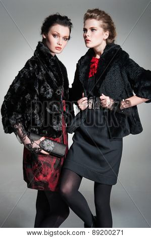 portrait of a young two woman with fur coat ,a purse posing