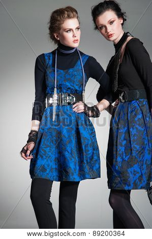 Young fashion two girl wearing fashion clothes on gray background