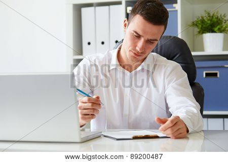 Young Businessman Signs A Document At The Office