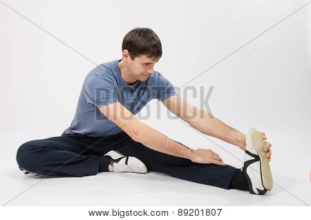 The Young Man Stretches Muscles Of Left Leg