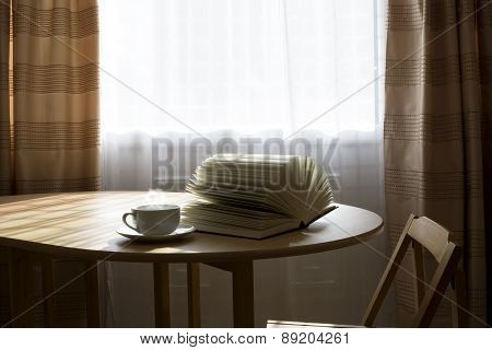 Open Book And A Cup Of Hot Drink On A Table
