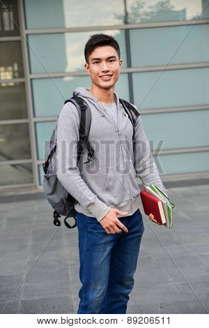 Portrait of college student holding book at college