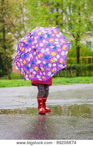 Back view of toddler girl with umbrella