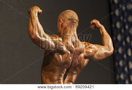Bodybuilder On Stage Demonstrating His Body and Muscles Standing Turned Backwards