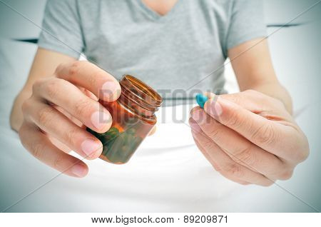a young caucasian man in pajamas in bed about to take a blue pill from a brown bottle