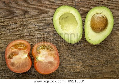 avocado and tomato cut in half on a grunge wood with a copy space