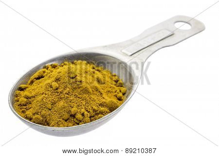 turmeric root powder on measuring tablespoon isolated with a clipping path
