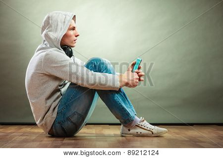 Hooded Man With Headphones Listening Music