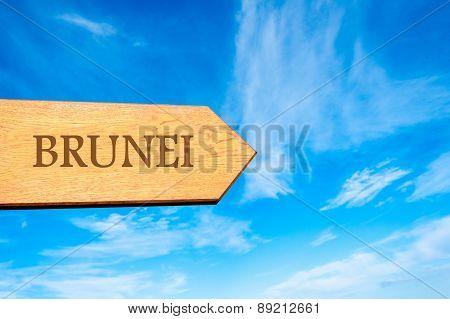 Wooden arrow sign pointing destination BRUNEI