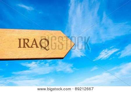 Wooden arrow sign pointing destination IRAQ
