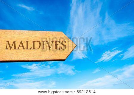 Wooden arrow sign pointing destination MALDIVES