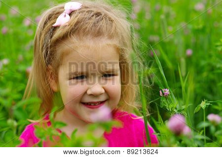 Cute little girl on the meadow in spring day. Child on field .