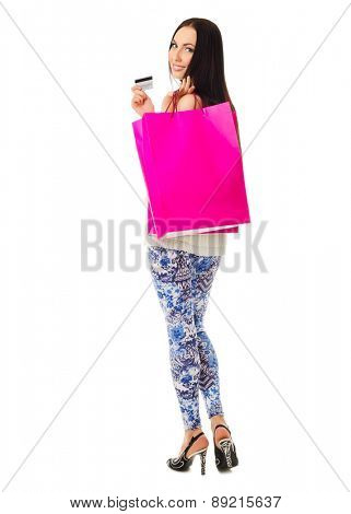 Young smiling girl with red paper bags and credit card isolated