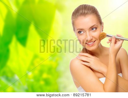 Healthy woman with makeup brush on floral background