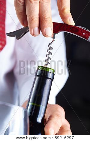 man opening a bottle of wine