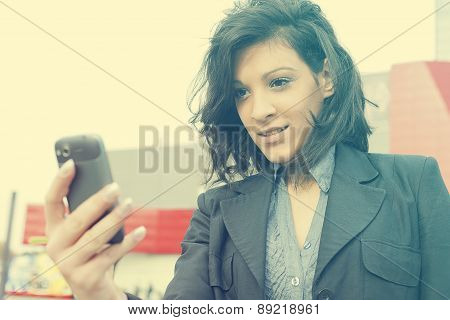 Young Woman With Cell Phone Walking, Blured Business Building In Background