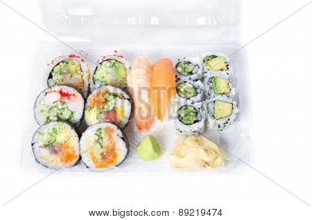 Assorted Sushi Rolls And Nigiri In A Transparent Plastic Tray Against White Background