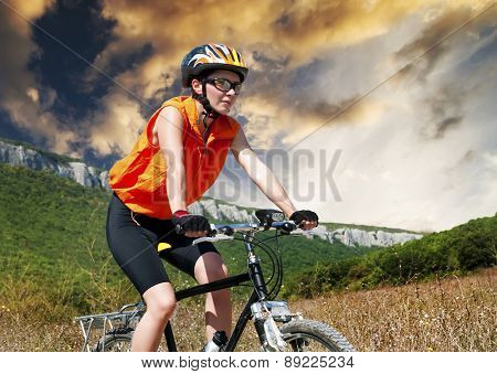 A young female riding a mountain bike outdoor at sunset