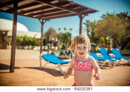 little cheerful girl running around the pool