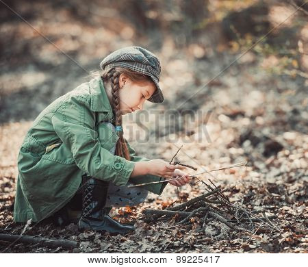 little girl making a bonfire, photo in vintage style