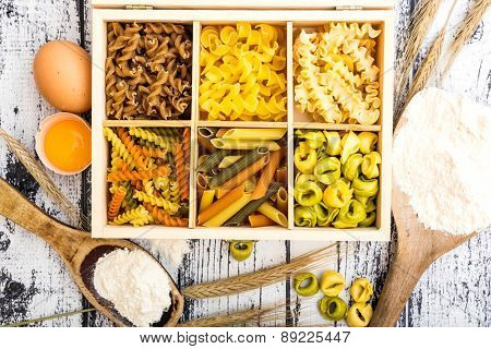 six types of pasta, tortellini and other products on textured wooden table