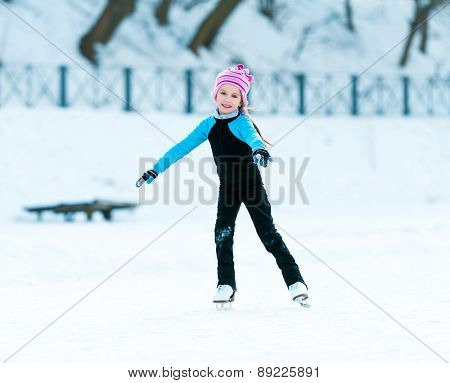 happy little girl in thermal suits skating in winter outdoors