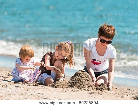 happy family: mother and two cute daughters playing in the sand