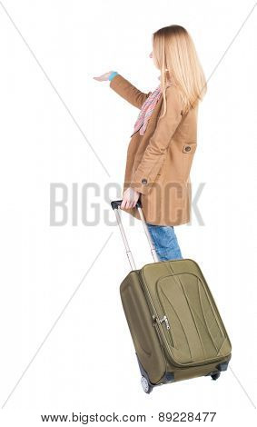Back view of  pointing woman with suitcase looking upbackside view of person. Isolated over white background. Pretty girl in a striped dress stands with a suitcase and looking at something