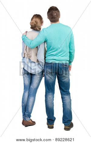 Back view of young embracing couple (man and woman) hug and look into distance. Rear view people collection. .  Isolated over white background. Guy hugs the girl in the shoulder vest.