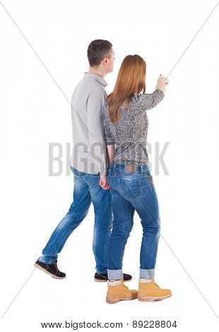 Back view of walking young couple (man and woman) pointing. Rear view people collection. backside view of person.  pressed shoulders man and woman go and point out the finger on the target path