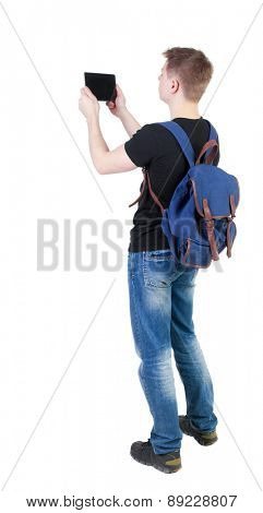 Back view of standing young man with tablet computer and backpack. Rear view people collection.  backside view of person.  Isolated over white background.