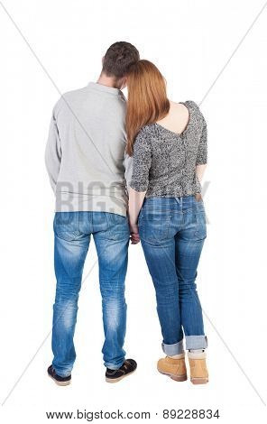 Back view of young embracing couple  hug and look into distance. beautiful friendly girl and guy together.   backside view of person.  Isolated over white background. Boy and girl on a date