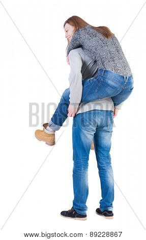 Back view of young embracing couple (man and woman) hug and look into the distance. beautiful friendly girl and guy together.   Isolated over white background. Man carries in her arms the girl.