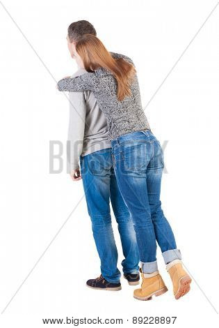 Back view of young embracing couple  hug and look into the distance. beautiful friendly girl and guy together.  Isolated over white background. Girl standing on tiptoes and hugs from behind Man.