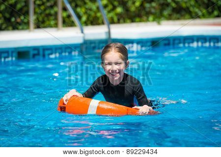 happy little girl swims in a wetsuit in the pool in  summer