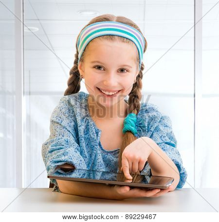 Cute happy little girl with her tablet